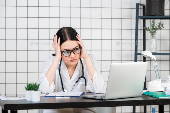 Desperate female doctor sitting at her office - Stock Photo - Images
