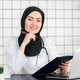 Portrait Of Smiling Muslim Female Doctor at her office - PhotoDune Item for Sale