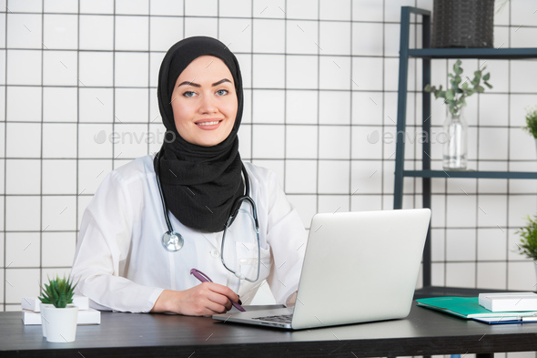 Muslim Female Doctor at her desk. White Background - Stock Photo - Images