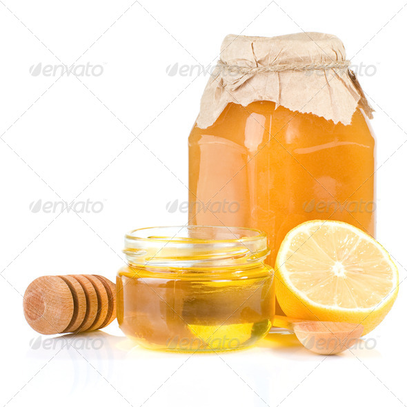 jar full of honey and lemon on white - Stock Photo - Images
