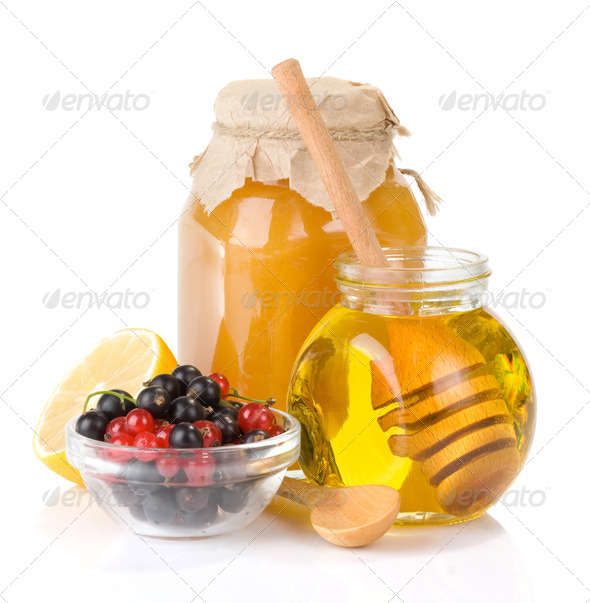 glass jar full of honey and berry - Stock Photo - Images