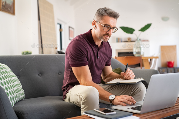 Busy businessman working on laptop at home - Stock Photo - Images