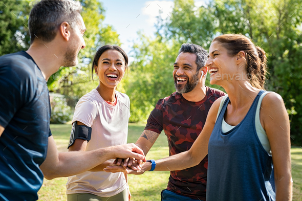Group of active mature friends in park stacking hands after workout - Stock Photo - Images
