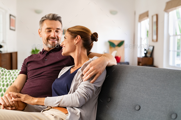 Mature couple in love sitting on couch - Stock Photo - Images