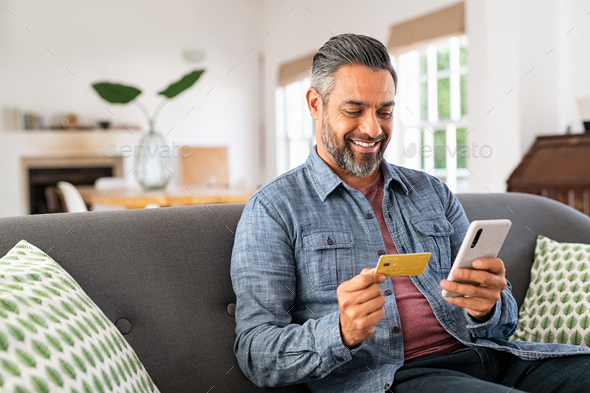 Mixed race man paying online on mobile phone - Stock Photo - Images