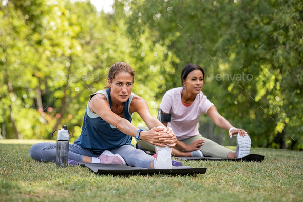 Two women doing stretching exercise at park - Stock Photo - Images