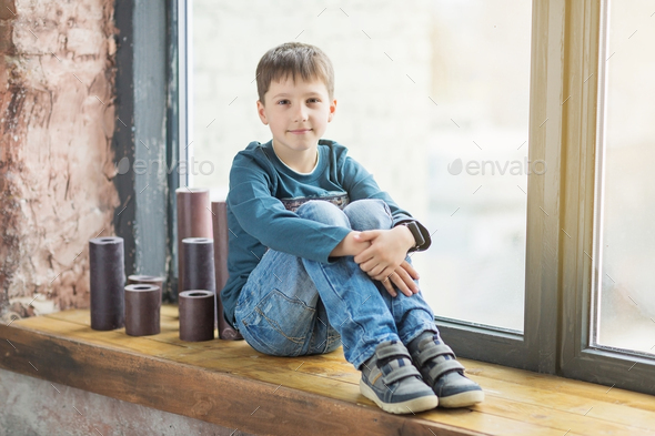teen boy sitting behind the window and smile - Stock Photo - Images