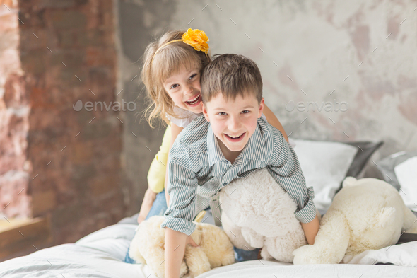 Brother and sister playing with teddy bear in bed - Stock Photo - Images