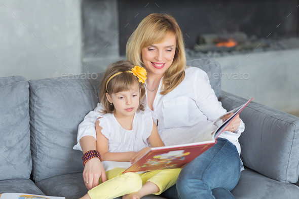 Mother and little daughter are playing, reading a book, sitting and enjoying in a sofa. - Stock Photo - Images