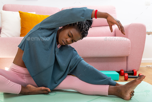 African female sitting on mat and stretching before workout at home - Stock Photo - Images