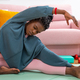 African female sitting on mat and stretching before workout at home - PhotoDune Item for Sale