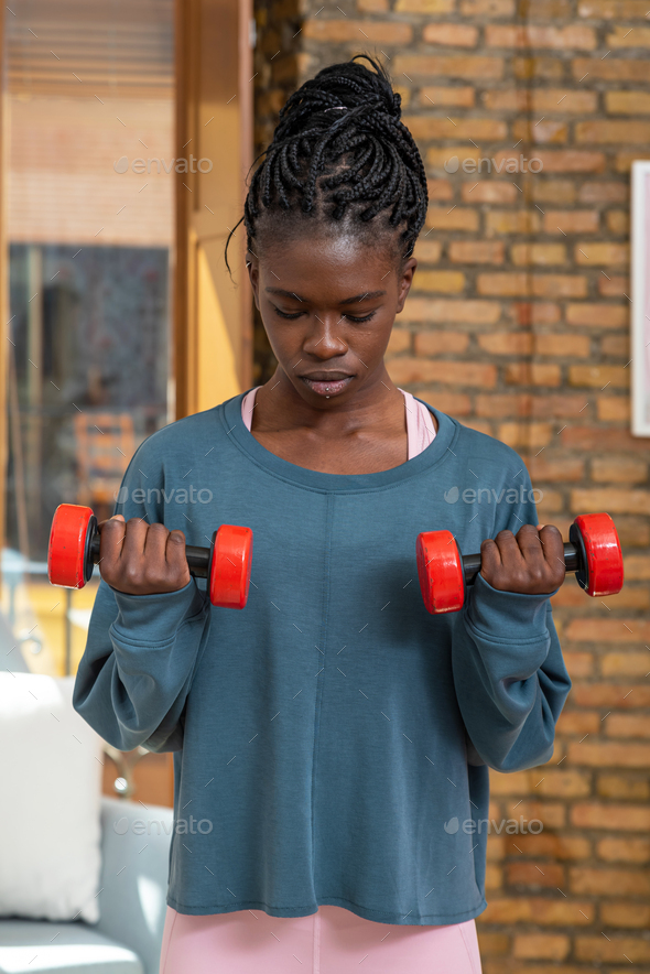 Focused black sportswoman doing exercises with dumbbells at home - Stock Photo - Images