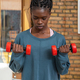 Focused black sportswoman doing exercises with dumbbells at home - PhotoDune Item for Sale