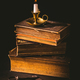 Pile of old antique books with candle in vintage style on black background - PhotoDune Item for Sale