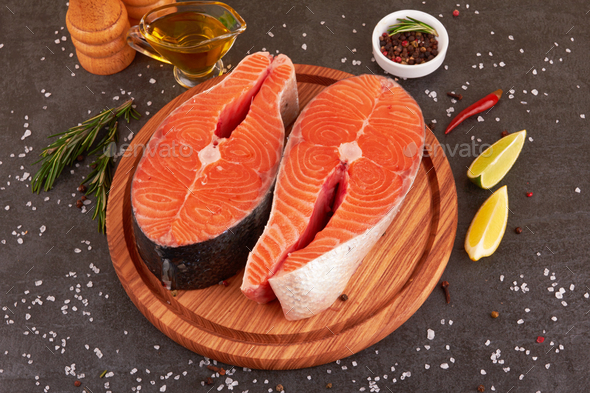 Salmon steak on a black background with spices - Stock Photo - Images