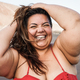 Plus size woman smiling on camera wearing bikini with beach in background - Focus on face - PhotoDune Item for Sale