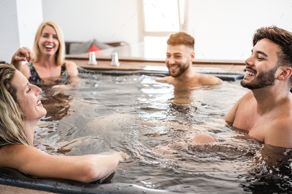 Gruop of friends having fun and relaxing in hot tub indoors at private village party - Stock Photo - Images