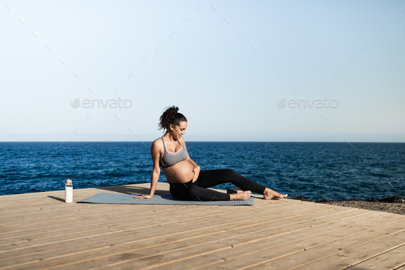 Young pregnant woman doing yoga outdoor - Stock Photo - Images