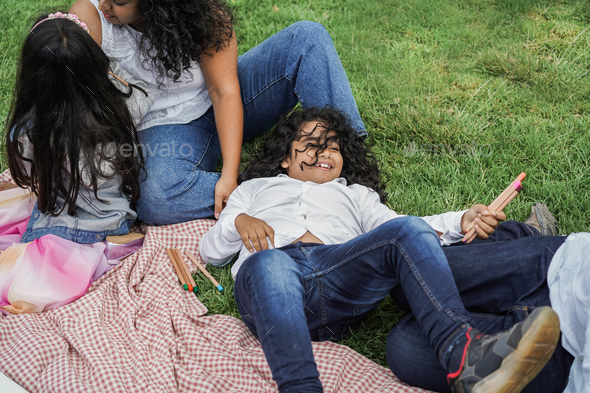 Happy indian family having fun at city park painting and laughing together - Stock Photo - Images