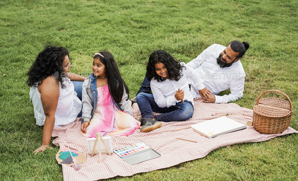 Happy indian family having fun painting with children outdoor at city park - Stock Photo - Images