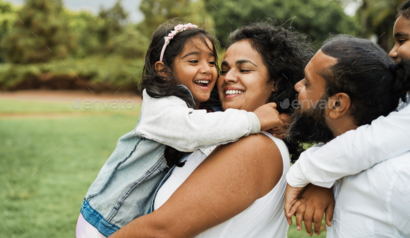 Happy indian family having fun outdoor - Hindu parents laughing with their children at city park - Stock Photo - Images