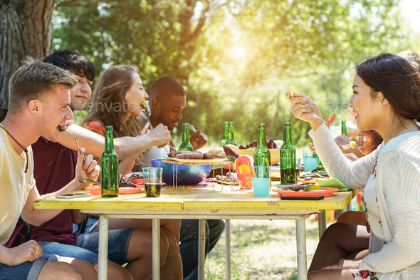 Happy multiracial friends doing picnic outdoor - Stock Photo - Images