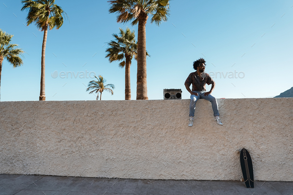 Young african man listening music with vintage boombox stereo with palms in background - Stock Photo - Images