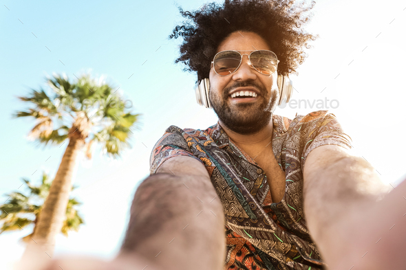 African american man listening music with headphones outdoor with palm trees in background - Stock Photo - Images