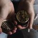 Man holding grinder with crushed weed - Alternative medicine, stoner and cannabis concept - PhotoDune Item for Sale