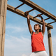 African young woman climbing monkey bars in military training boot camp outdoors at city park - PhotoDune Item for Sale