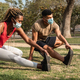 Multiracial people doing stretching routine outdoor at city park wearing safety masks - PhotoDune Item for Sale
