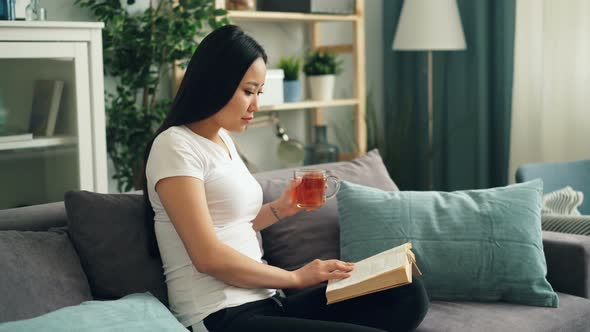 Good Looking Asian Woman Is Reading Book Enjoying Modern Literature Sitting On Sofa At Home Drinking Stock Footage
