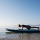 Fit young woman making a plank strength exercise on a sup board - PhotoDune Item for Sale