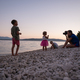 Young mother photographing her three children playing on pebble beach - PhotoDune Item for Sale