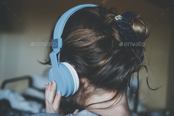Young woman listening to music and wearing cozy clothes - Stock Photo - Images