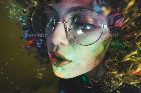 Young woman portrait illuminated by psychedelic lights - Stock Photo - Images