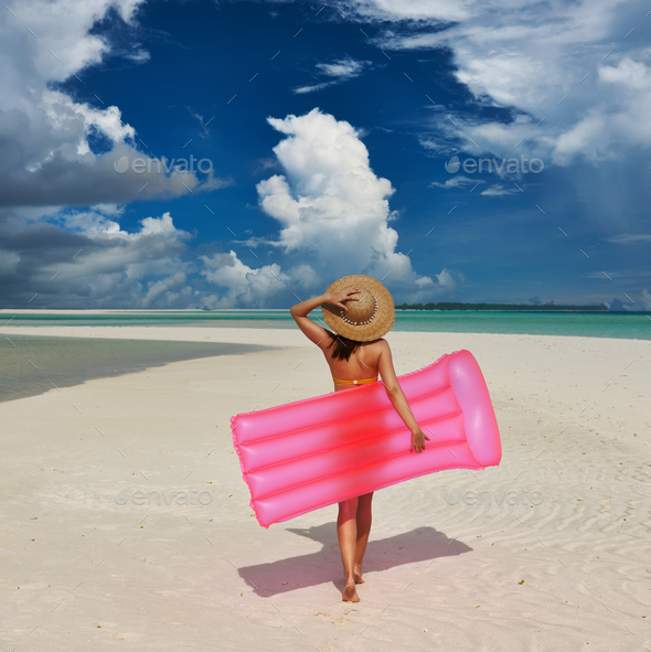 Woman with pink inflatable raft at the beach - Stock Photo - Images