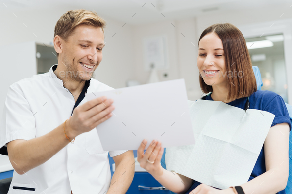 Dentist discussing with patient treatment plan - Stock Photo - Images