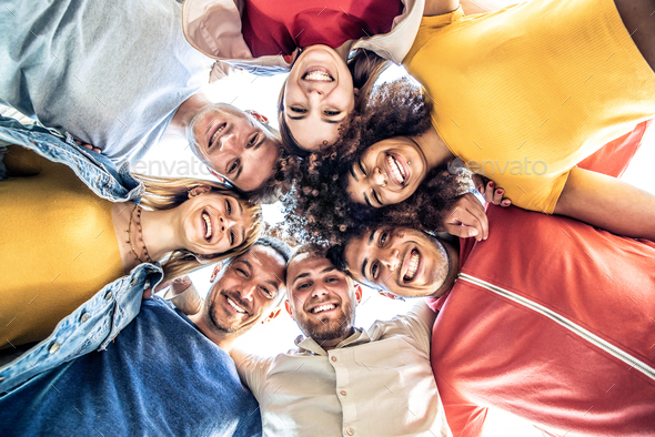 Multiracial group of young people standing in circle and smiling at camera - Stock Photo - Images