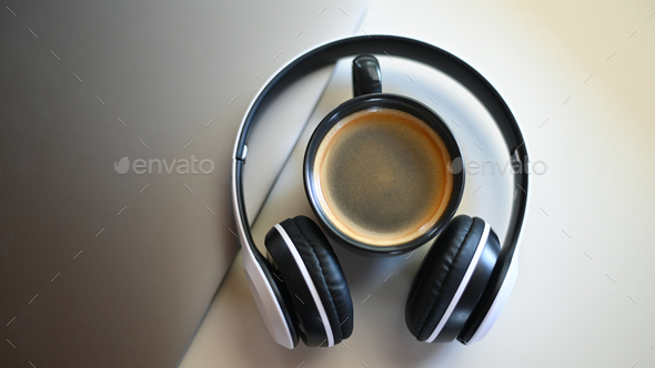 Coffee mug with laptop and headphone on placed on a table in a cafe,Coffee mug place in headphone. - Stock Photo - Images