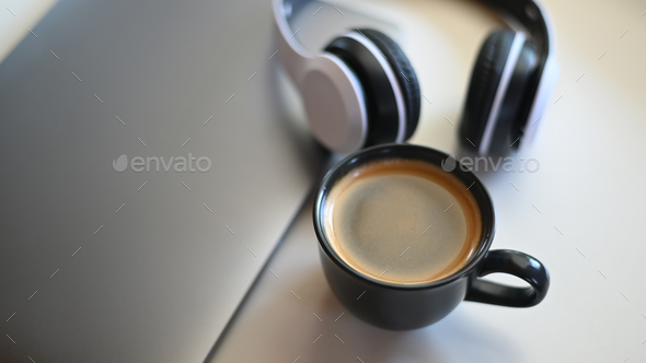 Coffee mug with laptop and headphone on placed on a table in a cafe. - Stock Photo - Images