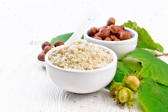 Flour and hazelnuts in bowls on white board - Stock Photo - Images