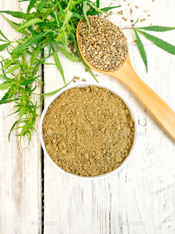Flour hemp in bowl with spoon and leaf on board top - Stock Photo - Images