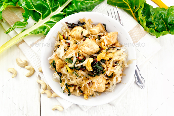 Funchoza with chard and meat in bowl on light board top - Stock Photo - Images