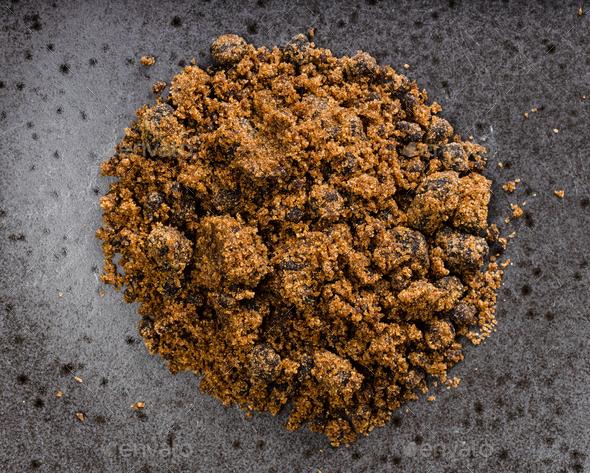 pile of dark muscovado cane sugar closeup on black - Stock Photo - Images