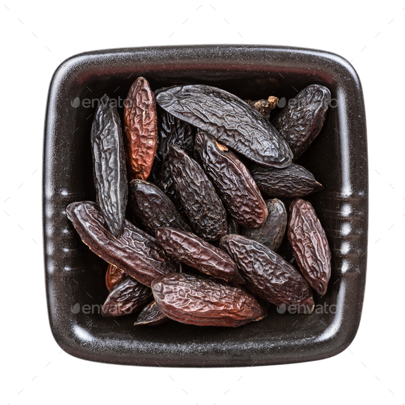 dried tonka beans in black bowl isolated - Stock Photo - Images