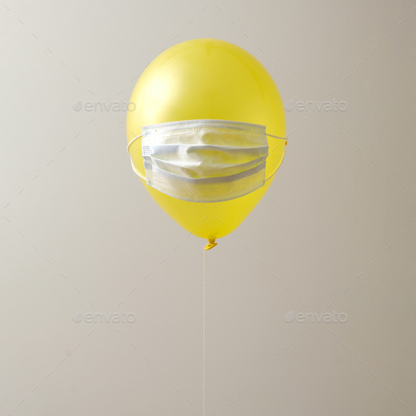 Yellow air balloon on a gray background and a protective mask - Stock Photo - Images