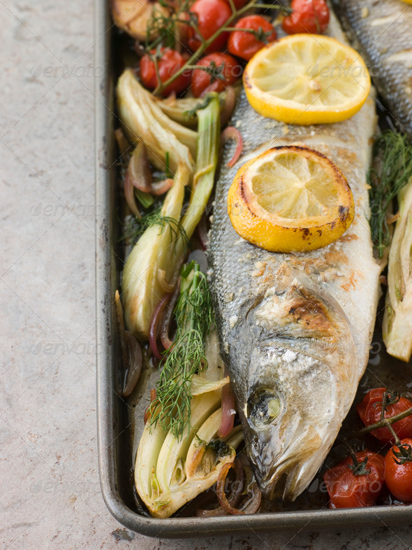 Whole Sea Bass Roasted with Fennel Lemon Garlic and Cherry Tomatoes on the Vine - Stock Photo - Images