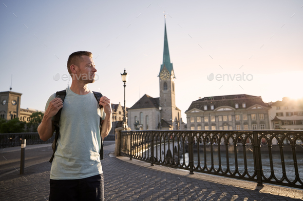 Man walking against cityscape of old town at sunset - Stock Photo - Images