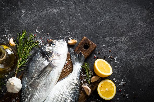 Fresh fish dorado on black stone table - Stock Photo - Images